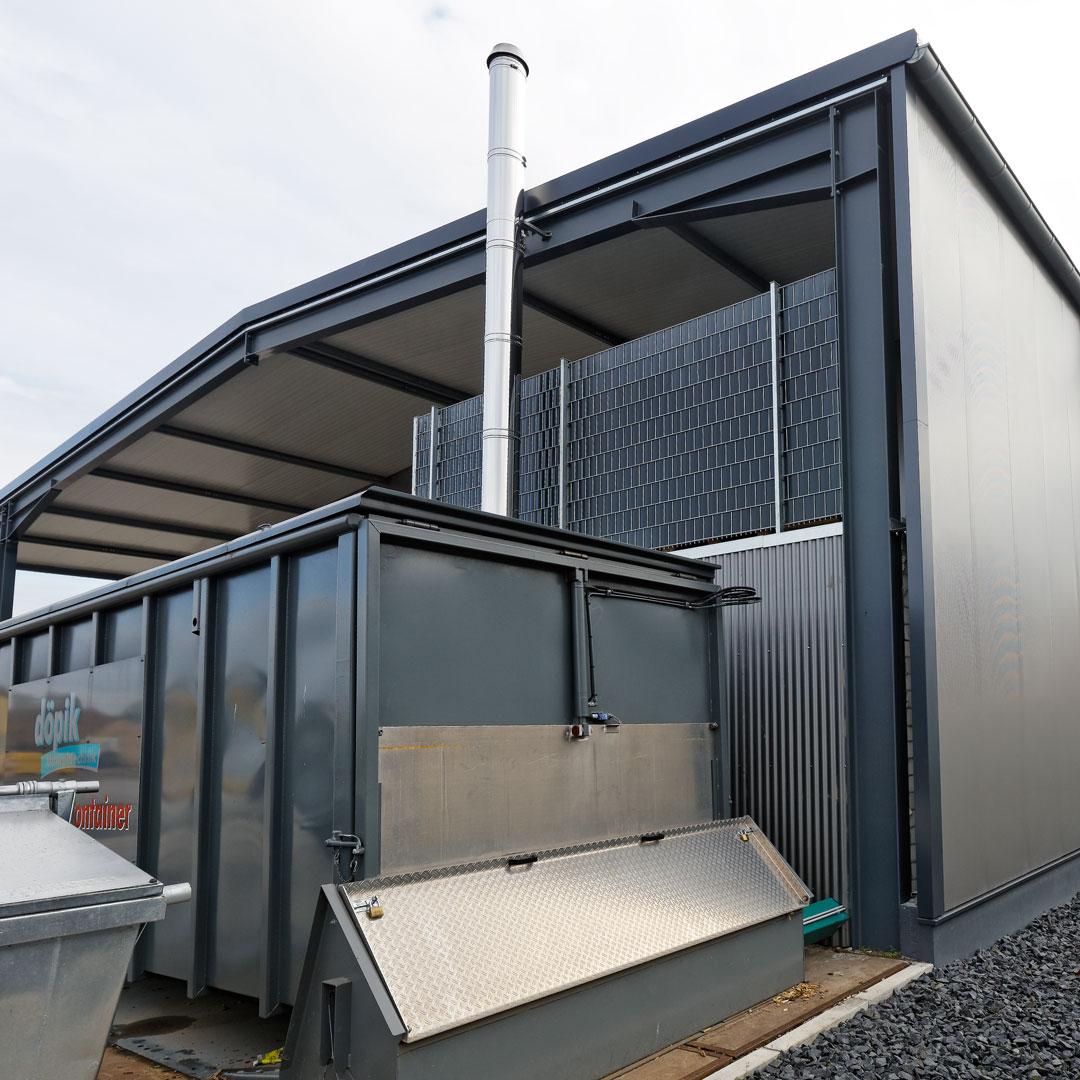Schubbodencontainer mit Edelstahlkamin vor einer Industriehalled